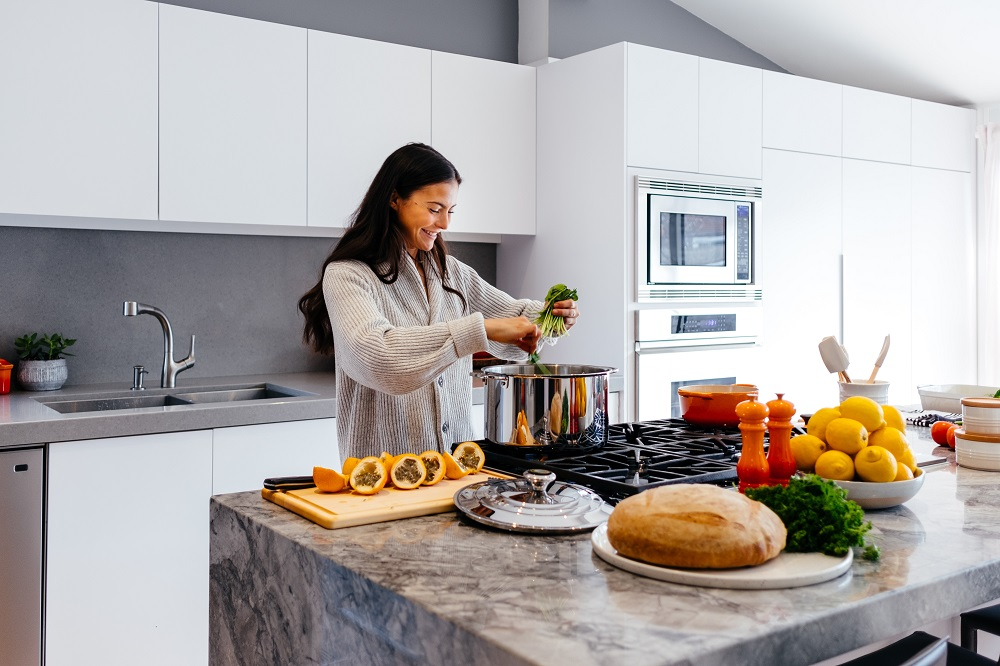 woman smiling in kitchen cooking a meal