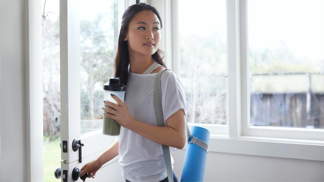 asian woman holding water and a yoga mat leaves her home