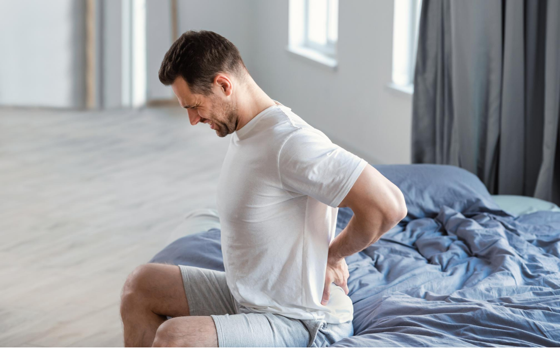 middle-aged man sits up in bed clenching his lower-back in pain