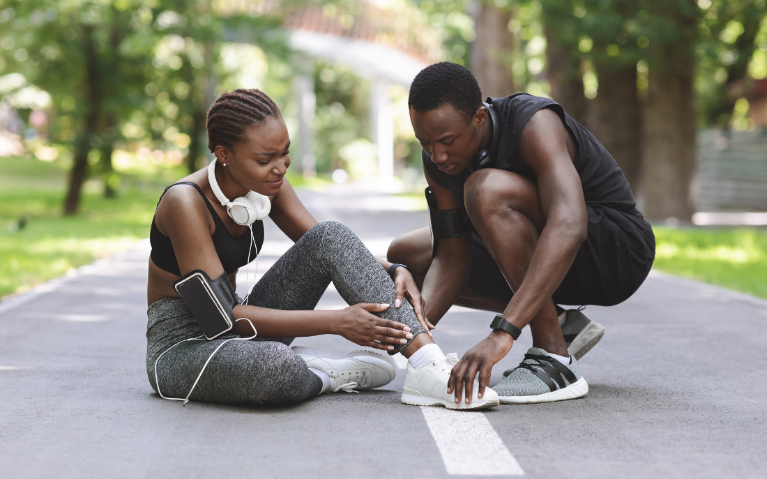 a couple of joggers stop on the road to tend to one of their ankle injuries