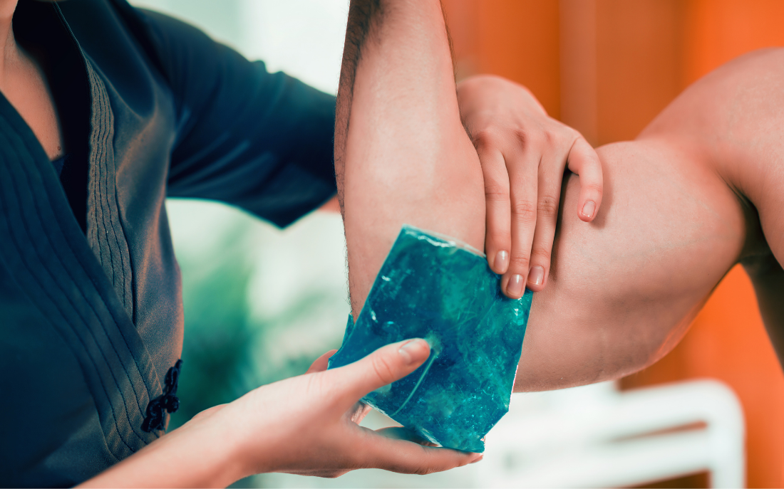 woman applying cold compress to man's elbow