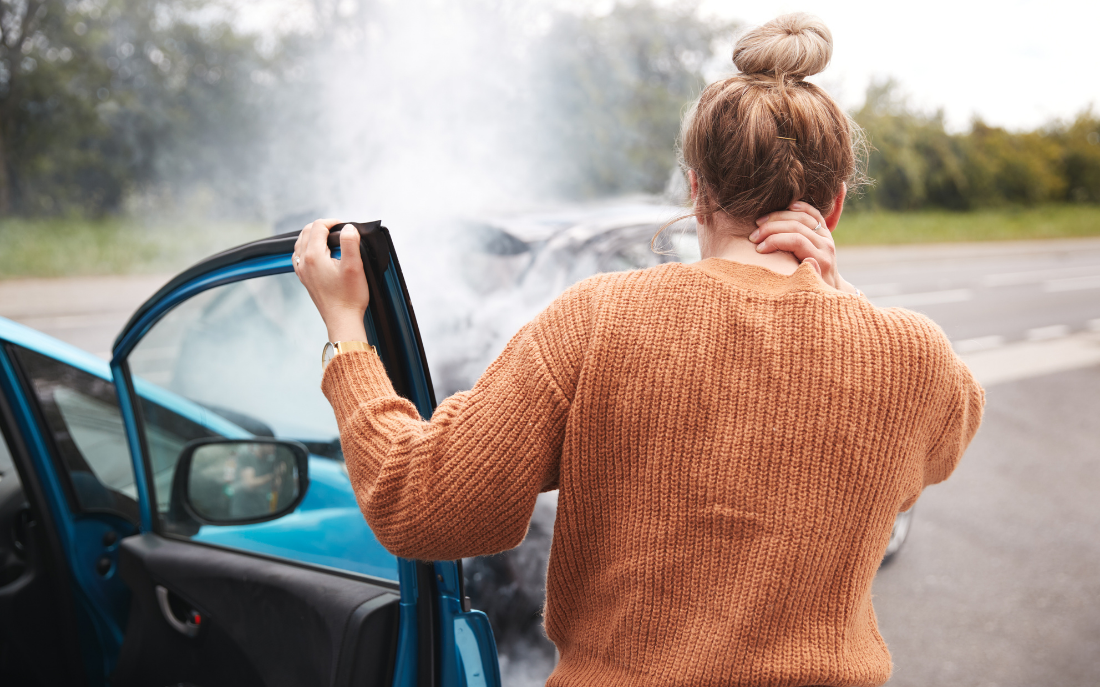blonde woman in an organge sweater steps out of her vehicle after a car accident clutching her neck