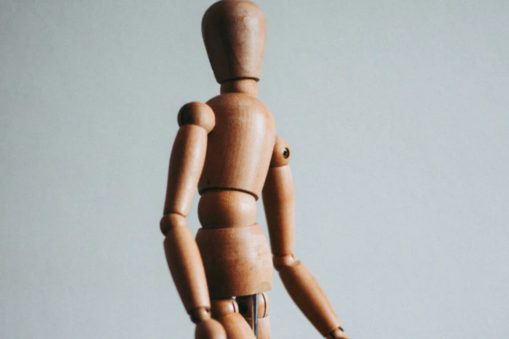 wooden figure standing infront of a white background