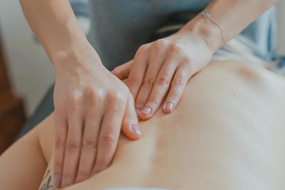 woman massaging her clients shoulder