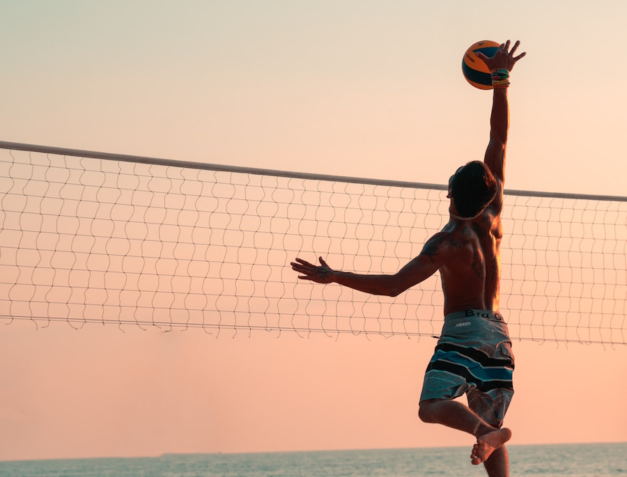 Man playing volleyball on the beach at sunset